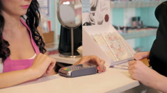 Profile view of a pretty young woman paying with a credit card at a store Stock Footage