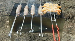Sausages grilling over the hot glowing coals Stock Footage