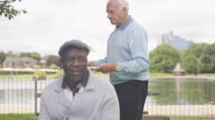 4K Happy senior male friends meeting up in the park to play draughts Stock Footage