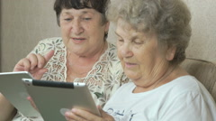 Old grandmothers holding silver digital tablets Stock Footage