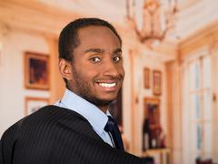 Headshot handsome man wearing business suit turning head and smiling to camera Stock Photos