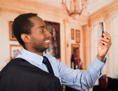 Headshot handsome man wearing business suit taking a selfie with mobile phone Stock Photos