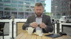 Businessman sits down for a tea, steadicam Stock Footage