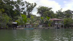 View from a boat of a village hut on stilts along a river in Guatemala. Stock Footage