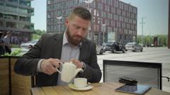 Businessman pours tea into cup, steadicam. Stock Footage