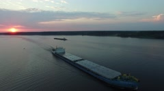 A barge floating on a wide river at sunrise. Aerial view. Stock Footage