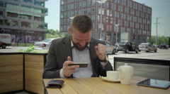 Happy businessman playing games on smartphone, steadicam Stock Footage