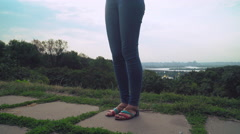 Young stylish girl standing on a hill and gaining a message on the phone Stock Footage