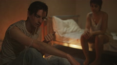 4K Drug addict couple in gloomy apartment injecting drugs & passing out Stock Footage