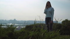 Beautiful young girl standing on the hill and talking on the phone Stock Footage