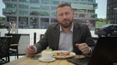 Businessman eating lunch, smiling for camera, steadicam. Stock Footage