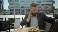 Businessman answers phone call and checks data in laptop, steadicam shot. Stock Footage