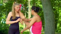 Personal trainer helping girl in leg stretching workout. Fitness workout outdoor Arkistovideo