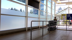 Young worker pushing trolleys walking through the doors at superstore Stock Footage