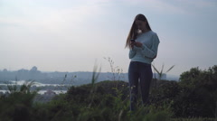 A young girl stands on a hill and looking at your phone Stock Footage