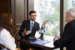Three Business People Negotiating at Table Stock Photos