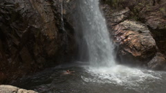 Guy Swims in River Pool at Waterfall Foot in Park Stock Footage