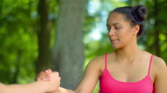 Young afro american woman doing stretching exercises with fit girl in park Stock Footage