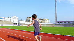 6 years old boy running in a stadium Stock Footage
