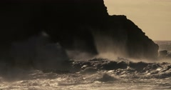 Huge ocean waves roll and crash into a rocky shore in slow motion. Stock Footage