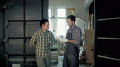 Two woodworkers in factory discussing in about something Stock Footage