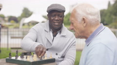 4K Happy senior male friends relaxing in the park playing chess Stock Footage