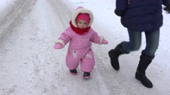 Little baby girl with mother walk on winter snowy road in park. 4K Stock Footage