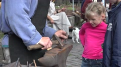 Young girl watching the work of the blacksmith. Stock Footage