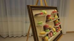 There is easel with macaroons served as picture of art Stock Footage