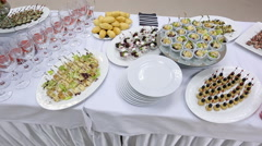 Up view of banquet table with appetizers, canapes, plates and glasses Stock Footage