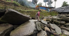 A Nepalese woman piles rocks in front of a makeshift tent home after becoming Stock Footage