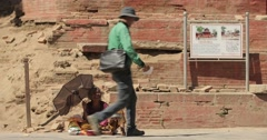 People walk past and ignore a homeless beggar on the streets of India or Nepal. Stock Footage