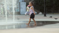 Cute baby girl running through fountain and laughs Stock Footage