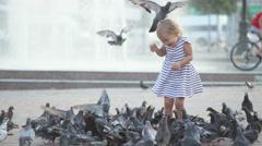 Little cute girl feeds pigeons near fountain Stock Footage