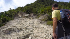 Male tourist hiking on rocky path Stock Footage