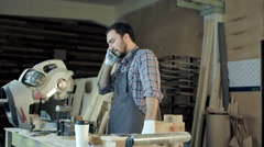 Carpenter working on his craft in a dusty workshop and speak phone Stock Footage
