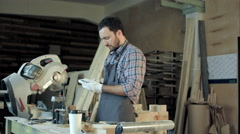 Carpenter with beard makes something on his smart phone in workshop Stock Footage
