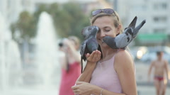Attractive young woman feeding pigeons in the park Stock Footage