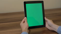 Man Using Tablet Zoom in hand with Green Screen on the Background of  Table Stock Footage