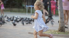 Little girl runs through a large group of pigeons. Stock Footage