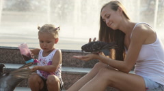 Mother and little girl in a park feeding pigeons. Stock Footage