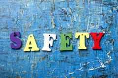 safety word written on wood abc letter at blue abstract background - stock photo