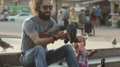 Man with daughter feeding pigeons in the park. Stock Footage
