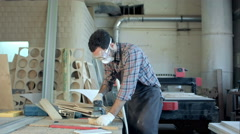 Bearded carpenter in safety glasses working with electric planer in workshop Stock Footage