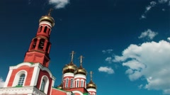 Stunningly beautiful church of red brick with gold domes against the clear blue  Stock Footage