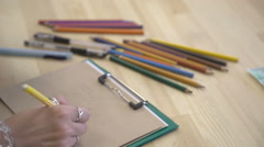 It is close-up image of artist hand, workplace with lots of colorful pencils Stock Footage