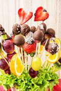 Fruit bouquet with chocolate frosting, special gift, vertical composition Stock Photos