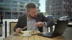 Businessman eating lunch is in hurry and goes away, steadicam. Stock Footage