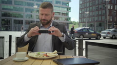 Businessman takes photo of the meal during lunch, steadicam. Stock Footage