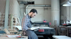 Bearded carpenter at his workshop reading diary Stock Footage